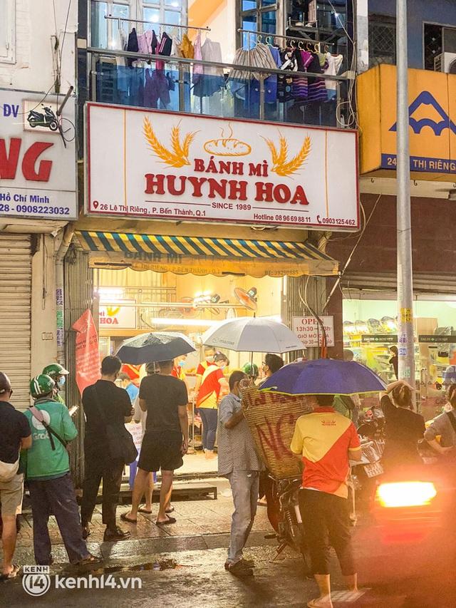 Hàng chục người xếp hàng dưới mưa mua ổ bánh mì đắt nhất Sài Gòn, có khách hốt chục cái ăn trả thù mùa dịch! - Ảnh 2.