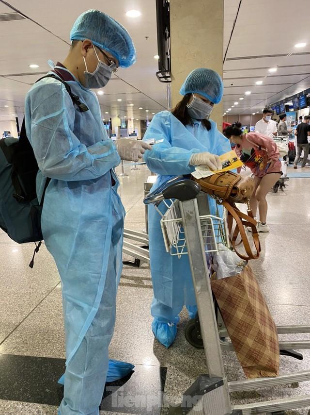 Hành khách mặc áo mưa, bảo hộ kín mít khi đi máy bay tại Tân Sơn Nhất - Ảnh 1.