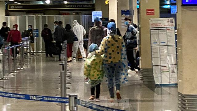 Hành khách mặc áo mưa, bảo hộ kín mít khi đi máy bay tại Tân Sơn Nhất - Ảnh 2.