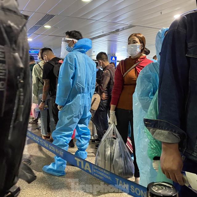 Hành khách mặc áo mưa, bảo hộ kín mít khi đi máy bay tại Tân Sơn Nhất - Ảnh 7.
