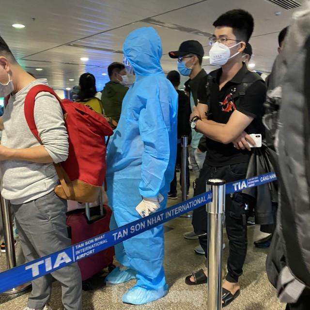 Hành khách mặc áo mưa, bảo hộ kín mít khi đi máy bay tại Tân Sơn Nhất - Ảnh 8.