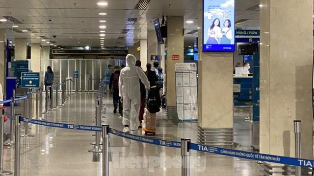Hành khách mặc áo mưa, bảo hộ kín mít khi đi máy bay tại Tân Sơn Nhất - Ảnh 10.