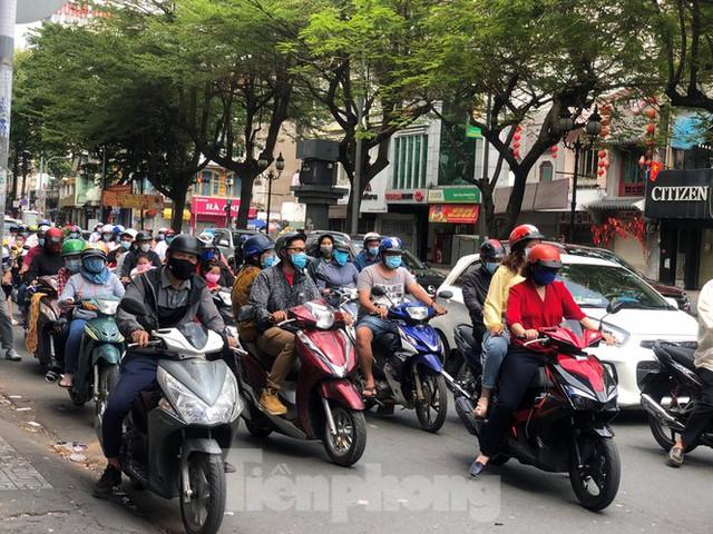 Sài Gòn nhộn nhịp trưa Mùng 1 Tết, dân đeo khẩu trang kín mít đi lễ chùa đầu năm - Ảnh 1.