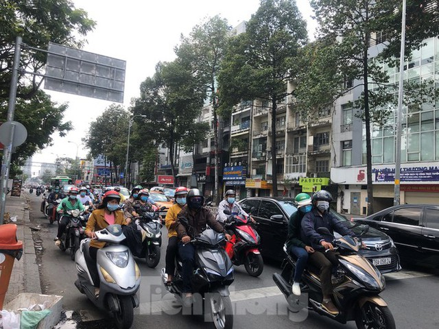 Sài Gòn nhộn nhịp trưa Mùng 1 Tết, dân đeo khẩu trang kín mít đi lễ chùa đầu năm - Ảnh 2.