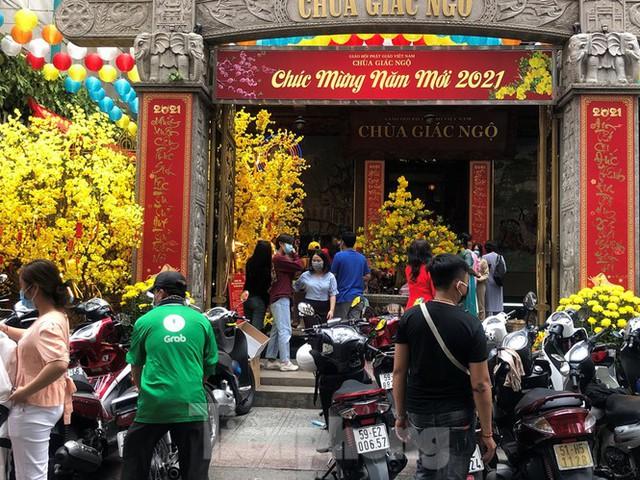 Sài Gòn nhộn nhịp trưa Mùng 1 Tết, dân đeo khẩu trang kín mít đi lễ chùa đầu năm - Ảnh 14.