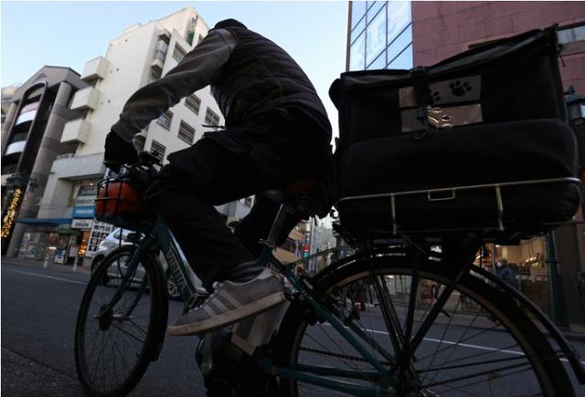 Bị Covid-19 dồn vào đường cùng, lao động trung niên Nhật Bản phải nai lưng làm shipper giao đồ ăn ngoài giờ để kiếm thêm thu nhập - Ảnh 1.