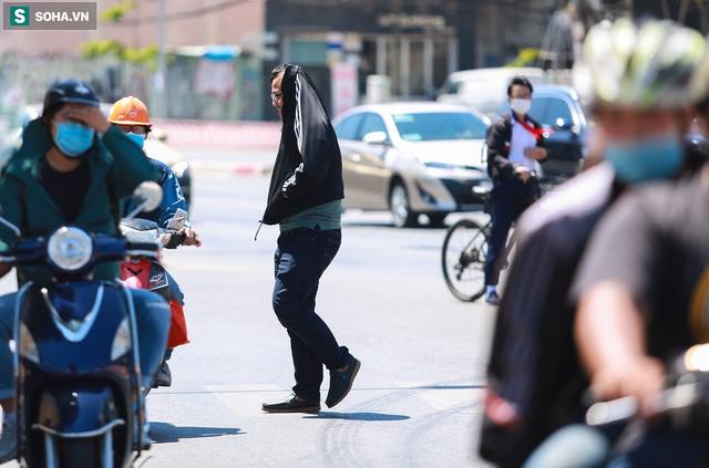 [ẢNH] Đường Sài Gòn nóng như thiêu, người dân vật vã tránh nóng ở góc cây, gầm cầu - Ảnh 5.