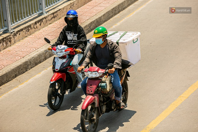 Chùm ảnh: Công nhân vật lộn với cái nóng hầm hập ở Sài Gòn, người đi đường mặc cả áo mưa tránh nắng - Ảnh 14.