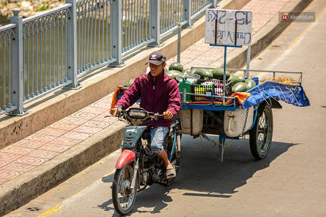 Chùm ảnh: Công nhân vật lộn với cái nóng hầm hập ở Sài Gòn, người đi đường mặc cả áo mưa tránh nắng - Ảnh 15.