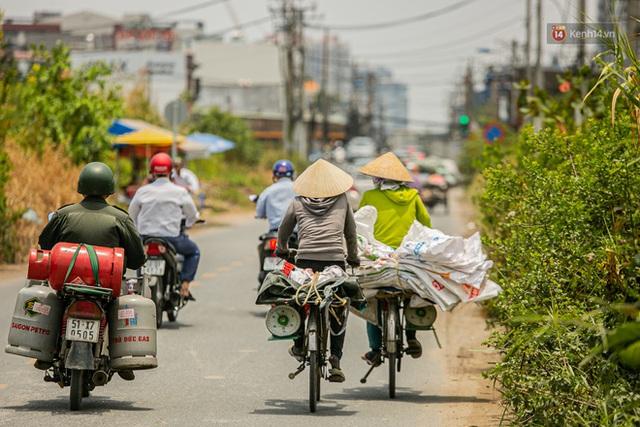 Chùm ảnh: Công nhân vật lộn với cái nóng hầm hập ở Sài Gòn, người đi đường mặc cả áo mưa tránh nắng - Ảnh 17.