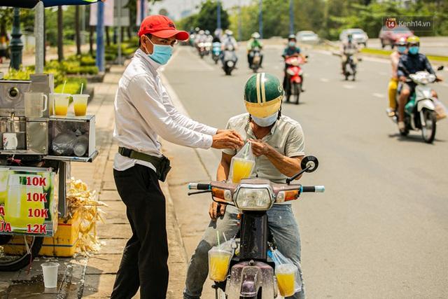 Chùm ảnh: Công nhân vật lộn với cái nóng hầm hập ở Sài Gòn, người đi đường mặc cả áo mưa tránh nắng - Ảnh 18.