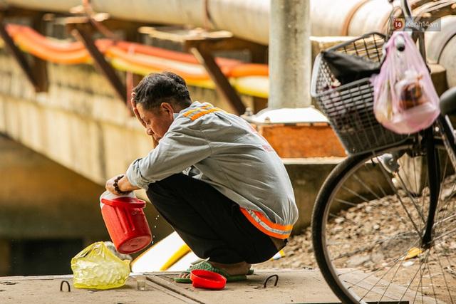 Chùm ảnh: Công nhân vật lộn với cái nóng hầm hập ở Sài Gòn, người đi đường mặc cả áo mưa tránh nắng - Ảnh 19.