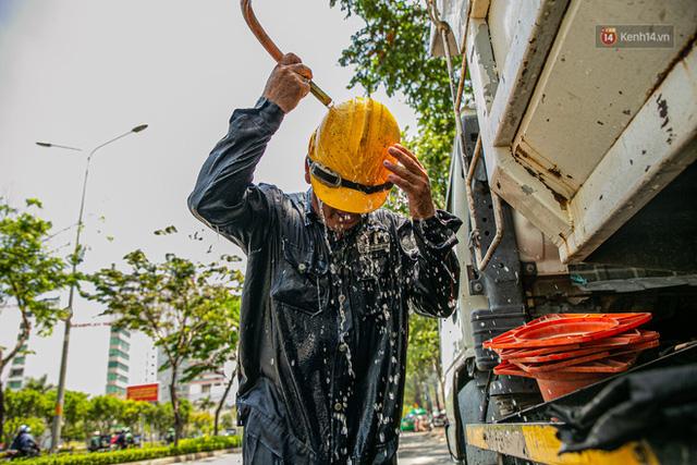 Chùm ảnh: Công nhân vật lộn với cái nóng hầm hập ở Sài Gòn, người đi đường mặc cả áo mưa tránh nắng - Ảnh 4.