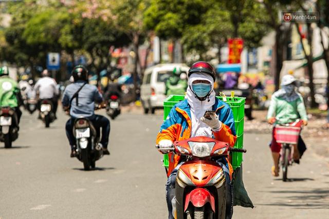 Chùm ảnh: Công nhân vật lộn với cái nóng hầm hập ở Sài Gòn, người đi đường mặc cả áo mưa tránh nắng - Ảnh 7.