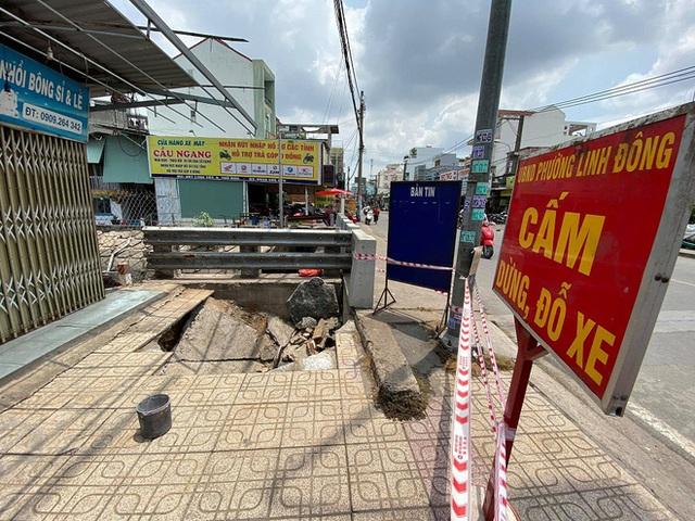 Hố tử thần bất ngờ xuất hiện nuốt chửng xe máy đậu trên vỉa hè ở Sài Gòn - Ảnh 2.
