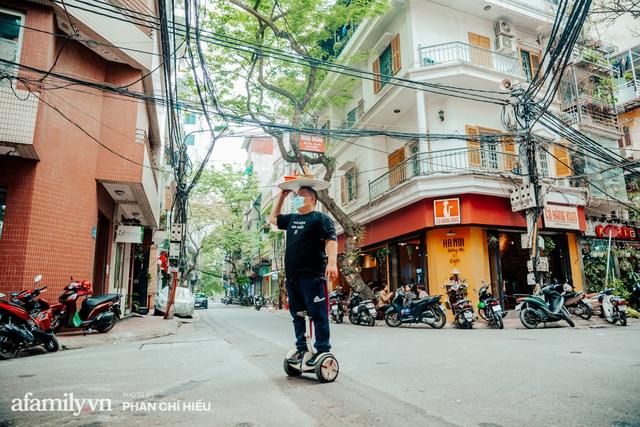 Quán phở diễn xiếc lạ nhất Hà Nội: Đội tô nước lèo nóng hổi thăng bằng trên đầu, chân lướt như bay bằng xe điện trong khu ngõ nhỏ để phục vụ khách - Ảnh 1.