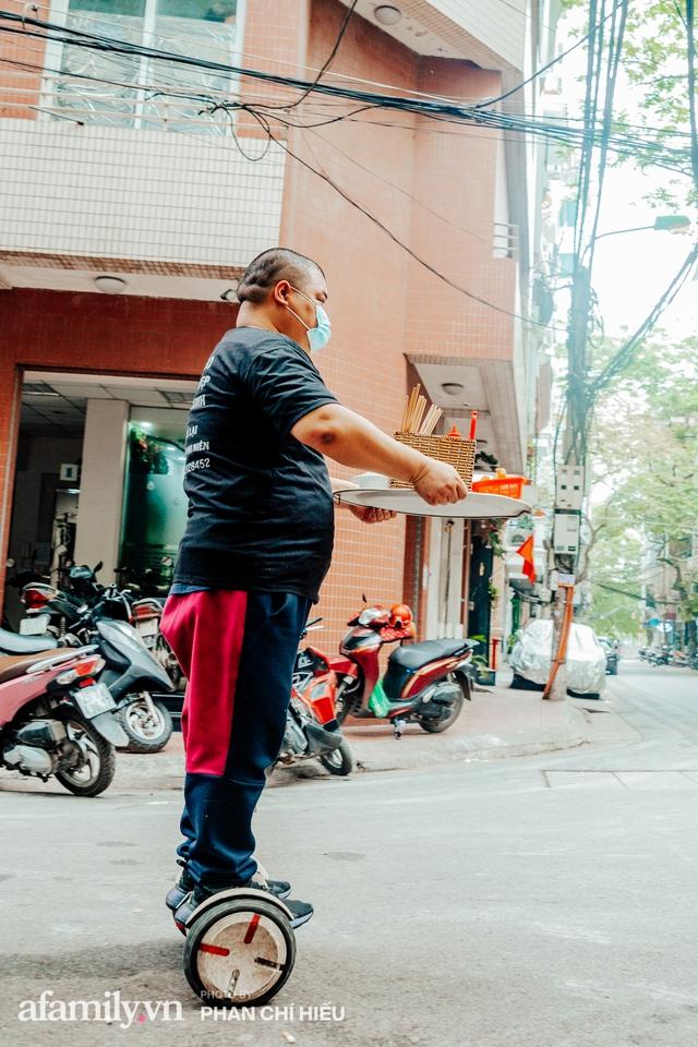 Quán phở diễn xiếc lạ nhất Hà Nội: Đội tô nước lèo nóng hổi thăng bằng trên đầu, chân lướt như bay bằng xe điện trong khu ngõ nhỏ để phục vụ khách - Ảnh 4.