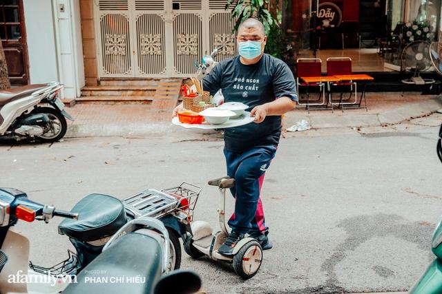 Quán phở diễn xiếc lạ nhất Hà Nội: Đội tô nước lèo nóng hổi thăng bằng trên đầu, chân lướt như bay bằng xe điện trong khu ngõ nhỏ để phục vụ khách - Ảnh 6.