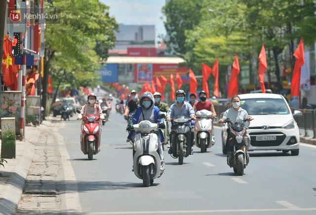 Nắng nóng đỉnh điểm từ đầu hè lên đến 40 độ C tại Hà Nội: Nhựa đường tan chảy, người dân dùng nước tưới đường giữa trưa - Ảnh 1.