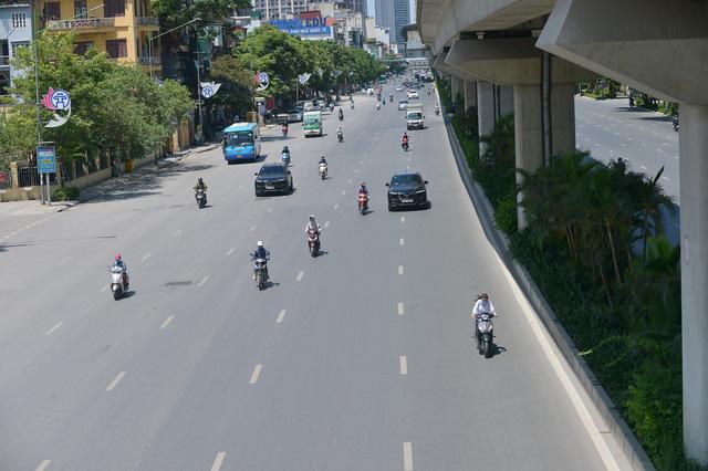 Nắng nóng đỉnh điểm từ đầu hè lên đến 40 độ C tại Hà Nội: Nhựa đường tan chảy, người dân dùng nước tưới đường giữa trưa - Ảnh 2.