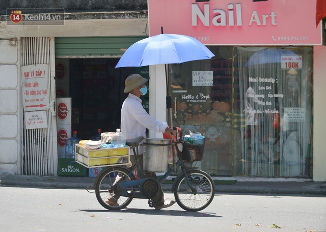 Nắng nóng đỉnh điểm từ đầu hè lên đến 40 độ C tại Hà Nội: Nhựa đường tan chảy, người dân dùng nước tưới đường giữa trưa - Ảnh 11.