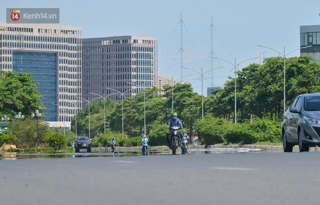 Nắng nóng đỉnh điểm từ đầu hè lên đến 40 độ C tại Hà Nội: Nhựa đường tan chảy, người dân dùng nước tưới đường giữa trưa - Ảnh 3.