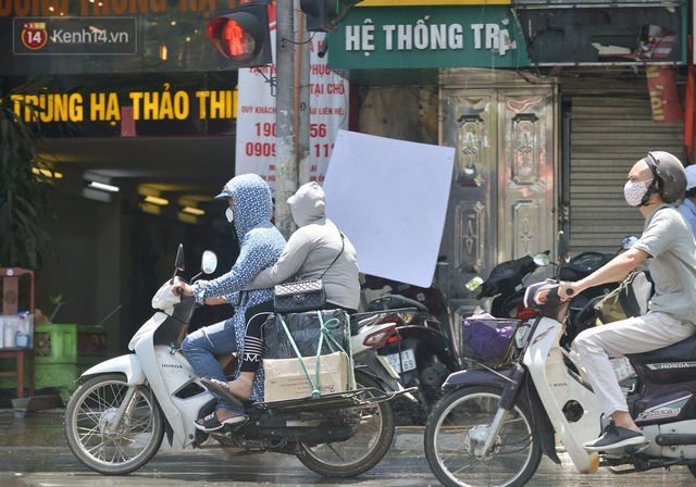 Nắng nóng đỉnh điểm từ đầu hè lên đến 40 độ C tại Hà Nội: Nhựa đường tan chảy, người dân dùng nước tưới đường giữa trưa - Ảnh 21.