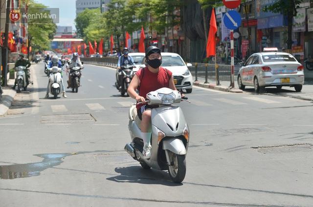 Nắng nóng đỉnh điểm từ đầu hè lên đến 40 độ C tại Hà Nội: Nhựa đường tan chảy, người dân dùng nước tưới đường giữa trưa - Ảnh 22.