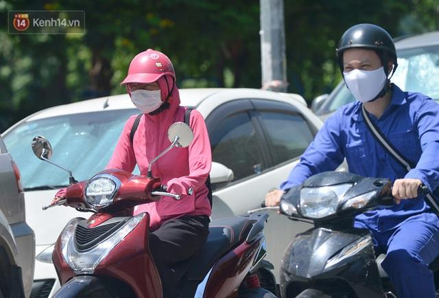 Nắng nóng đỉnh điểm từ đầu hè lên đến 40 độ C tại Hà Nội: Nhựa đường tan chảy, người dân dùng nước tưới đường giữa trưa - Ảnh 9.