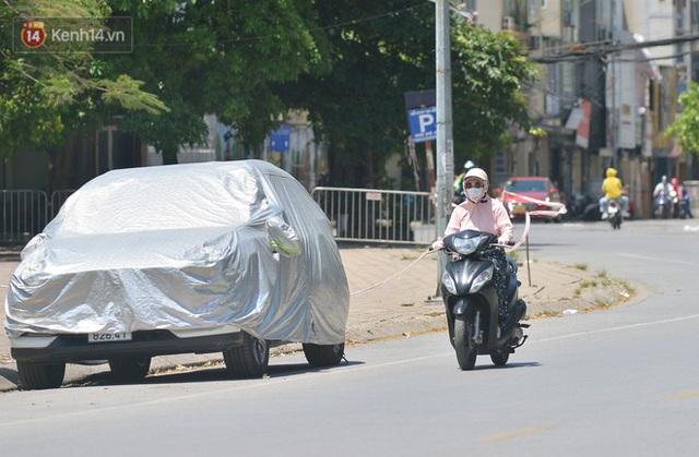 Nắng nóng đỉnh điểm từ đầu hè lên đến 40 độ C tại Hà Nội: Nhựa đường tan chảy, người dân dùng nước tưới đường giữa trưa - Ảnh 10.