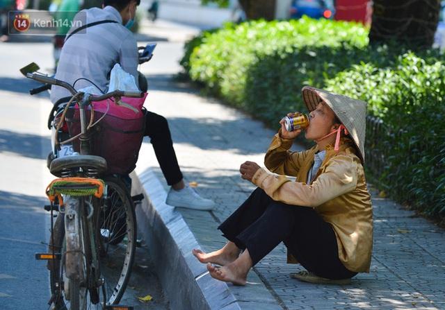 Nắng nóng đỉnh điểm lên đến gần 50 độ C tại Hà Nội: Mặt đường bốc hơi, người dân chật vật mưu sinh - Ảnh 7.