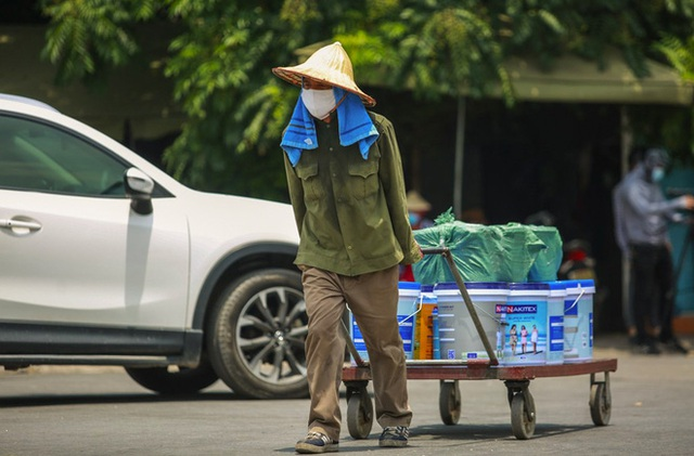 Nắng nóng đỉnh điểm lên đến gần 50 độ C tại Hà Nội: Mặt đường bốc hơi, người dân chật vật mưu sinh - Ảnh 8.