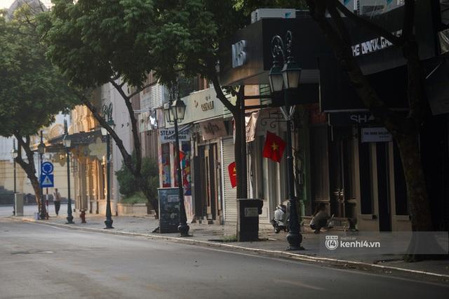 Hà Nội ngày đầu thực hiện giãn cách xã hội theo Chỉ thị 16: Đường phố vắng lặng, hàng quán đóng kín cửa im lìm - Ảnh 10.