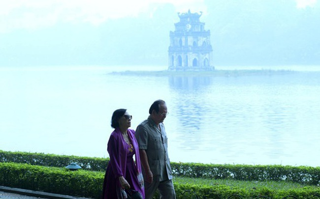 Phố phường Hà Nội chìm trong mịt mù sương, bụi dù vào giữa trưa