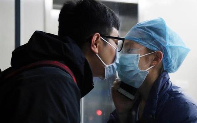 """Khoảnh khắc nữ y tá chống dịch virus corona hôn bạn trai qua tấm kính cách ly: """"Chờ em ra ngoài, mình đi đăng kí kết hôn nhé!"""""""