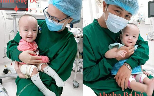 Cặp song sinh Trúc Nhi - Diệu Nhi cười tươi rạng rỡ, thích thú khi được bố mẹ ẵm bồng trên tay