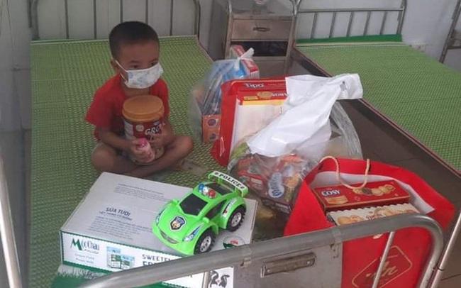 Xót xa hình ảnh cháu bé 4 tuổi mắc Covid-19 tay ôm khư khư hộp sữa, mặc đồ bảo hộ kín mít trong khu cách ly
