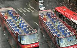 Hành khách mặc áo mưa trải nghiệm du lịch Hà Nội trên xe bus 2 tầng