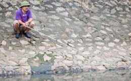 Người dân thư thả ngồi câu cá bên bờ sông Tô Lịch