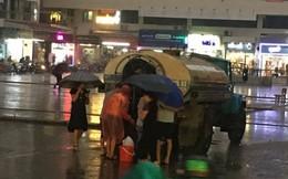 Cư dân Linh Đàm đội mưa nhọc nhằn hứng từng can nước